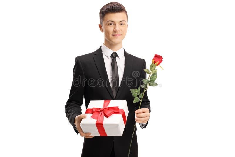 Elegantly stilig tonårs- pojke för påklädd som rymmer en gåva och ett r royaltyfria bilder