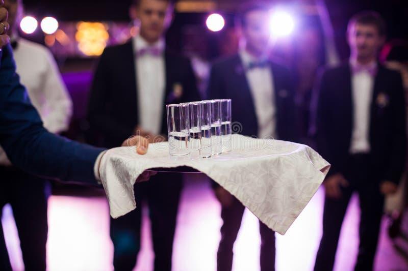 Elegantly tjänade som vodkaskott på uppläggningsfatet på weddinmottagandet arkivfoton