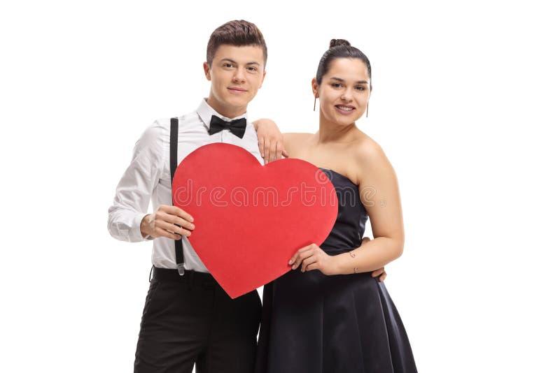 Elegantly tonårs- par för påklädd som rymmer en röd hjärta royaltyfria bilder