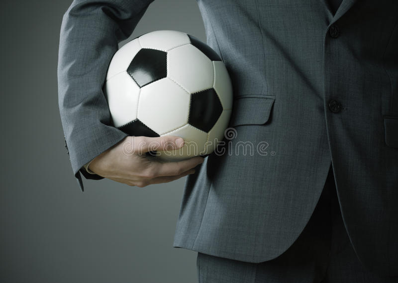 Elegantt affärsmaninnehav som en fotboll klumpa ihop sig arkivbilder