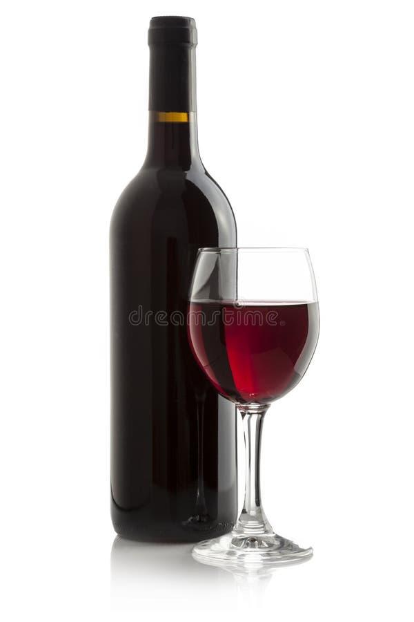 Elegantt rött vinexponeringsglas och en wine buteljerar   arkivfoto