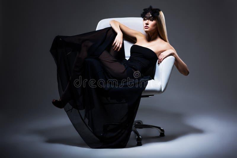 Godimento. Bionda di classe della donna elegante che si rilassa nella sedia. Vestito e maschera neri con le piume fotografia stock libera da diritti