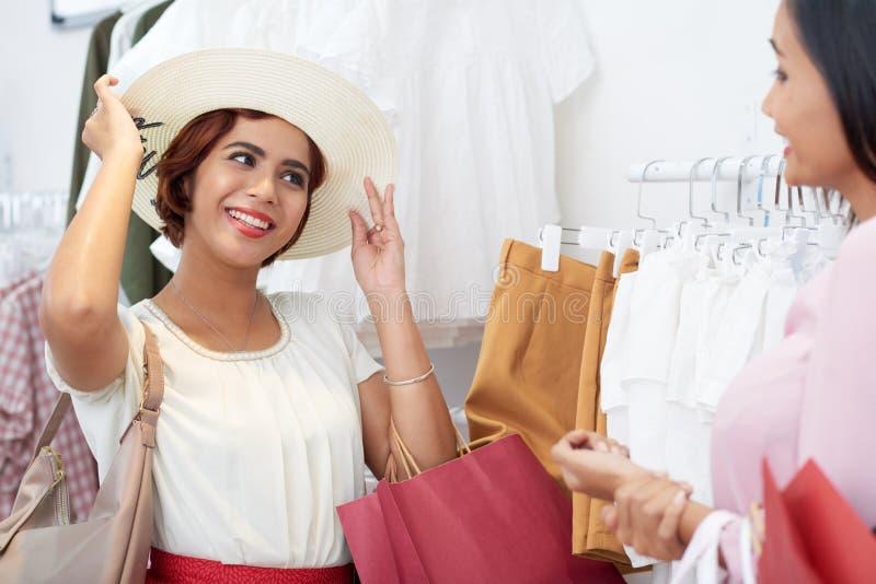 Elegir el sombrero en tienda foto de archivo