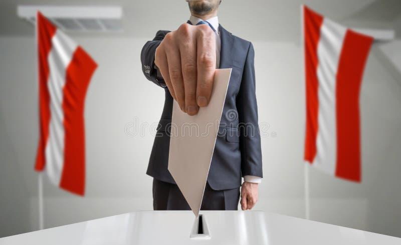 Eleição ou referendo em Áustria O eleitor guarda a cédula acima disponivel do envelope Bandeiras austríacas no fundo fotos de stock
