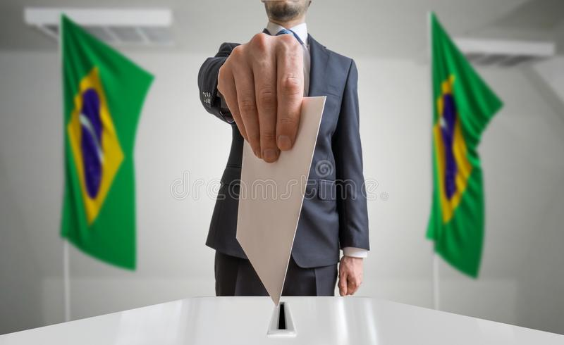 Eleição ou referendo em Brasil O eleitor guarda a cédula acima disponivel do envelope Bandeiras brasileiras no fundo imagem de stock royalty free