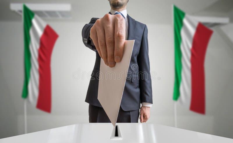 Eleição ou referendo em Itália O eleitor guarda a cédula acima disponivel do envelope Bandeiras italianas no fundo foto de stock