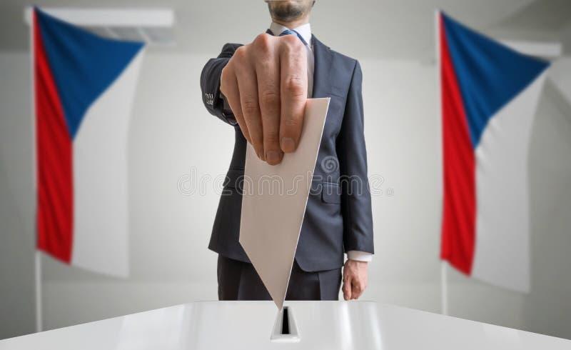 Eleição ou referendo em República Checa O eleitor guarda a cédula acima disponivel do envelope Bandeiras checas no fundo imagem de stock royalty free
