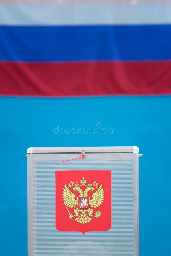 Eleição presidencial - caixa de votação com cédulas na frente da bandeira do russo imagem de stock