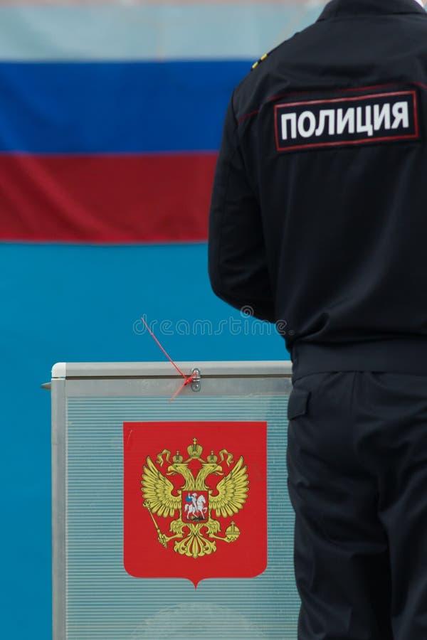 Eleição presidencial do russo - caixa de votação próxima do polícia com cédulas fotos de stock