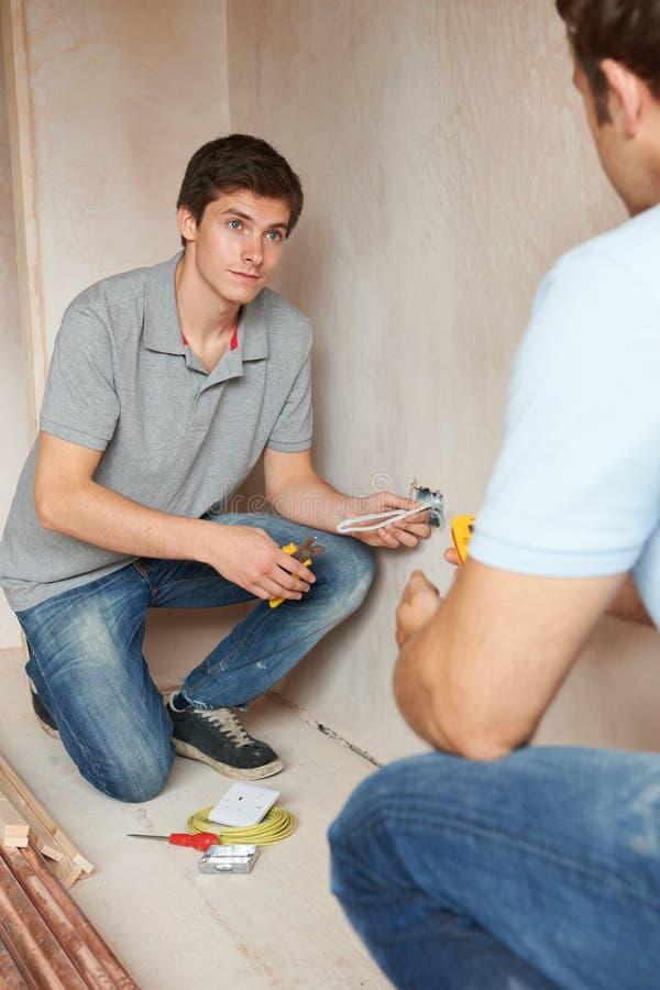 Elektricien With Apprentice Working in Nieuw Huis stock foto's