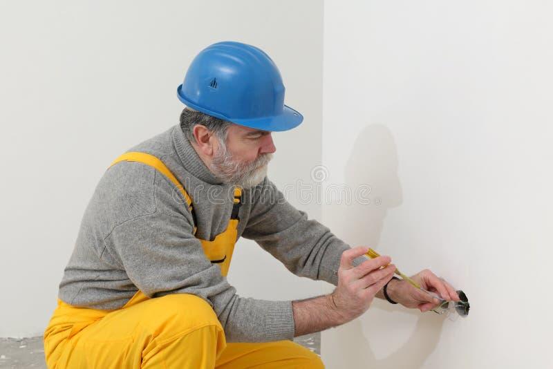 Elektricien bij bouwwerf testende installatie royalty-vrije stock afbeelding