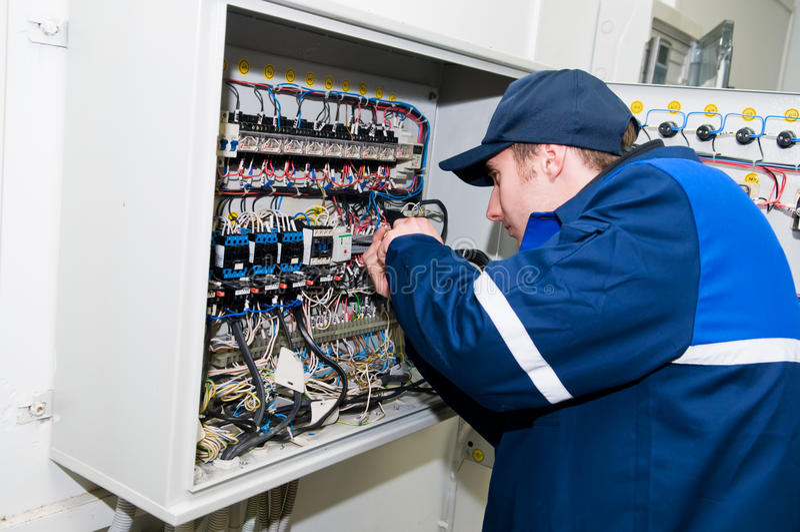 Elektricien bij voltage het aanpassen stock afbeeldingen
