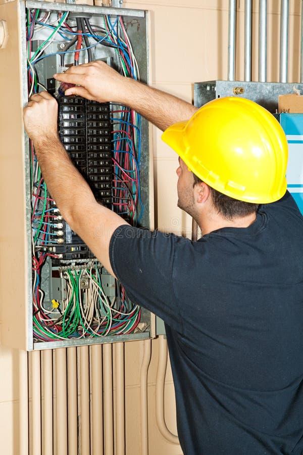 Elektricien die aan ElektroComité werkt stock afbeelding