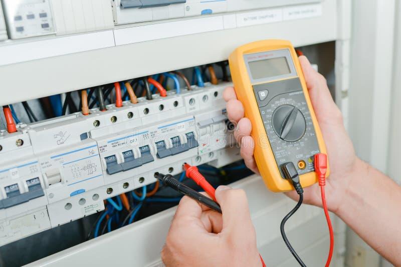 Elektricien die een fusebox controleren stock foto
