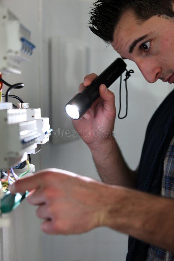 Elektricien die een toorts glanzen stock fotografie