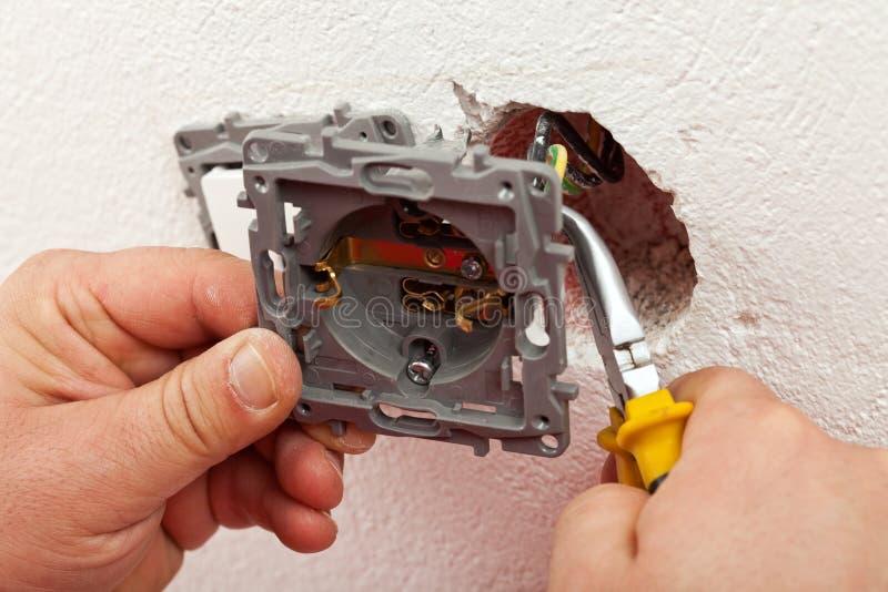 Elektricien die elektrische muurinrichting verbinden met de draden stock afbeelding