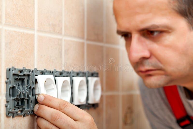 Elektricien die elektro van de muurinrichting of stop compone opzetten royalty-vrije stock fotografie