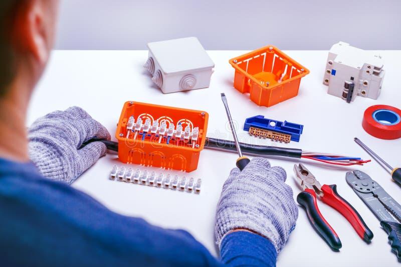 Elektricien die elektrodoos herstellen reparatie elektrisch materiaal elektrohulpmiddelen en component voor de dienst stock fotografie