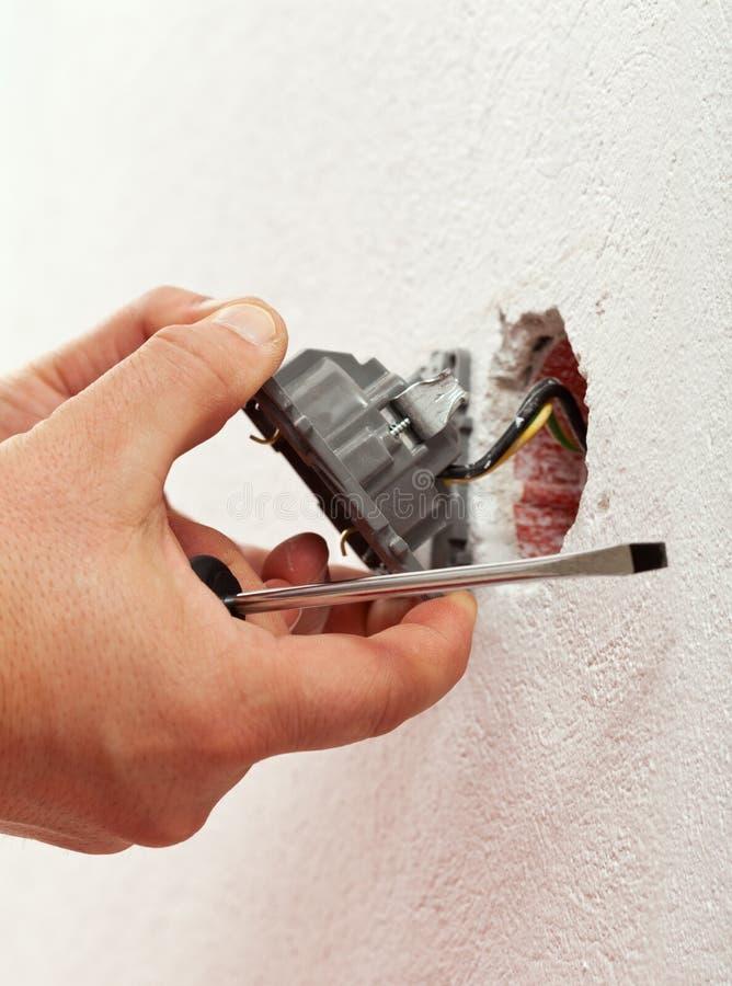 Elektricien die elektromuurinrichting opzetten stock fotografie