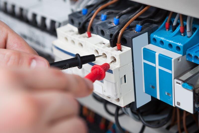 Elektricien die fusebox met multimetersonde onderzoeken stock afbeeldingen