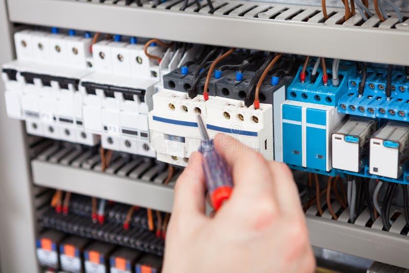 Elektricien die fusebox met schroevedraaier onderzoeken royalty-vrije stock foto's