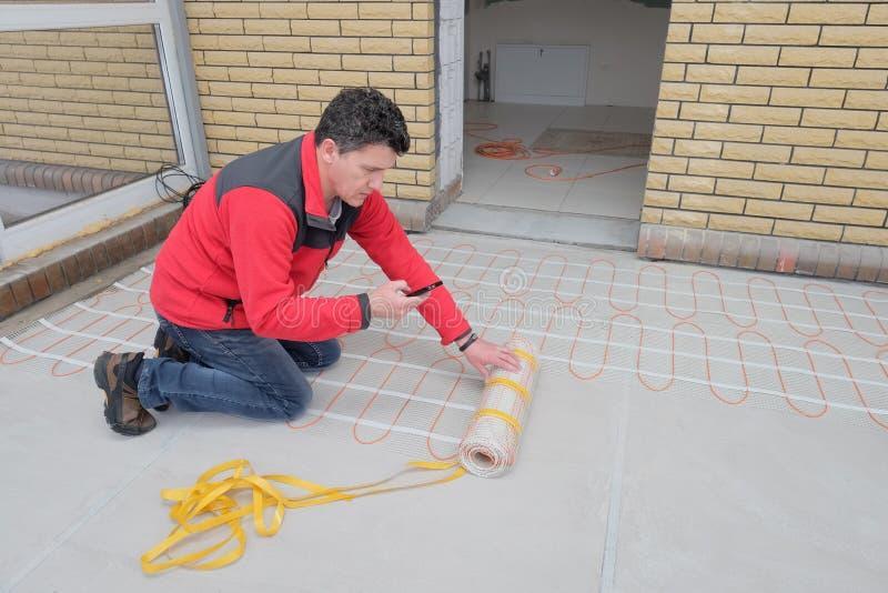 Elektricien die het verwarmen elektrokabel installeren op concrete vloer Mens gelezen instructie royalty-vrije stock afbeeldingen
