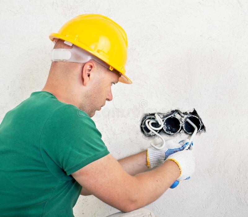 Elektricien die met mes een draad snijden stock foto