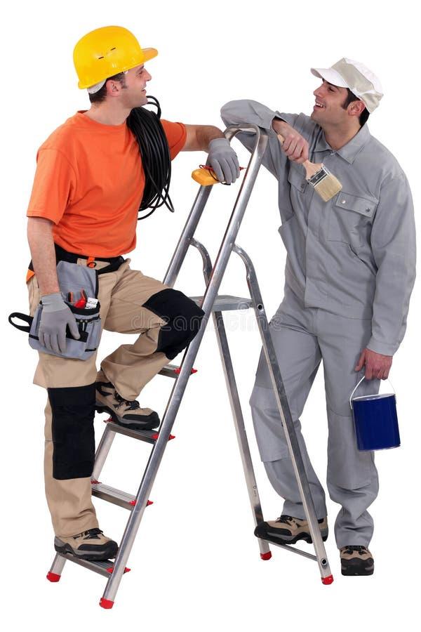Elektricien die met schilder wordt bevonden stock foto's