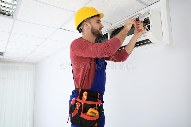 Elektricien die met schroevedraaier airconditioner herstellen stock afbeelding