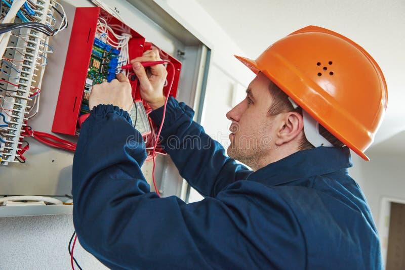 Elektricien die met schroevedraaierreparatie elektrische actuator in zekeringkast schakelen stock foto's