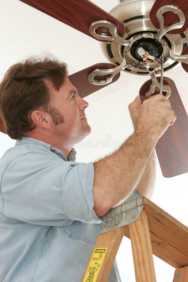Elektricien die Plafondventilator installeert stock afbeelding
