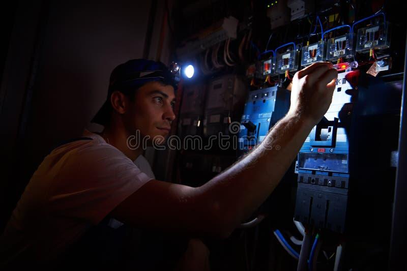 Elektricien die tijdens schade werken stock foto's