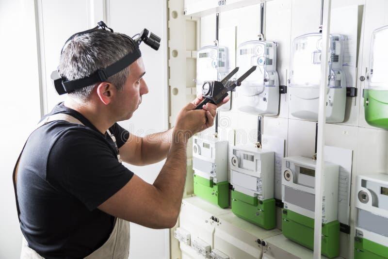 Elektricien het testen materiaal in de doos van de zekeringsschakelaar dicht omhoog stock afbeelding