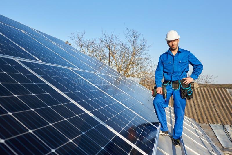 Elektricien opzettend zonnepaneel op dak van modern huis royalty-vrije stock afbeelding