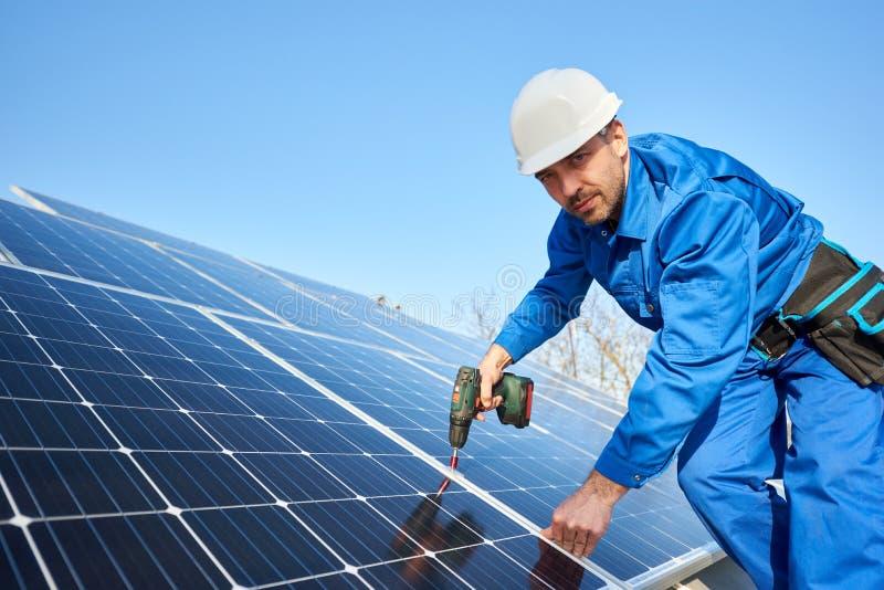 Elektricien opzettend zonnepaneel op dak van modern huis stock foto's