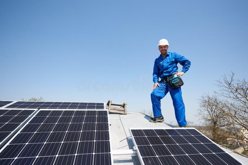 Elektricien opzettend zonnepaneel op dak van modern huis stock fotografie