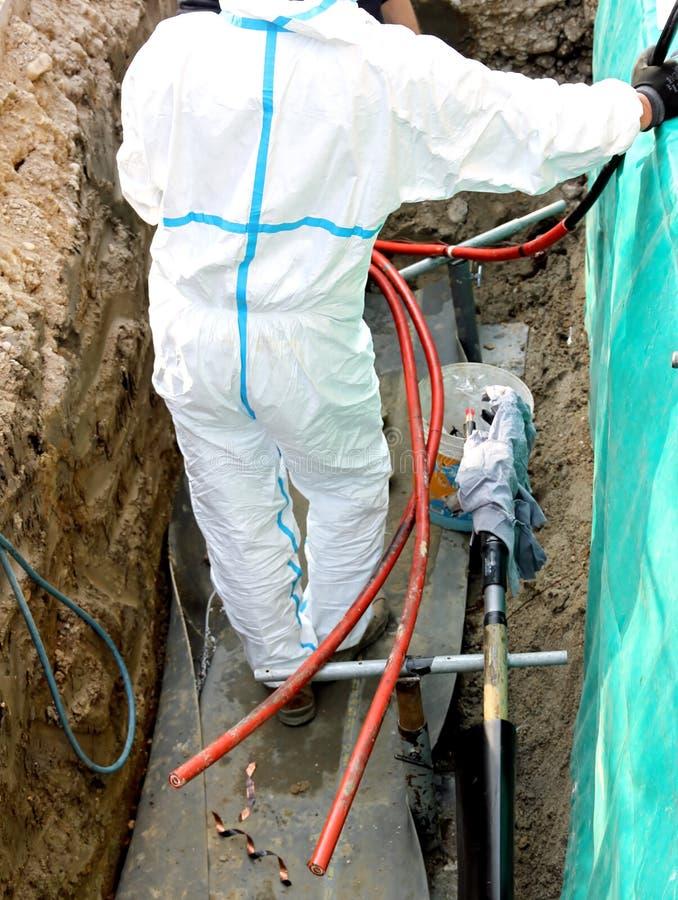 Elektricien tijdens de reparatiebaan van een kabel van de hoogspanningsmacht stock foto