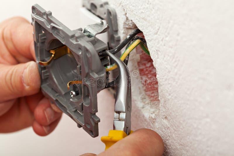Elektricienhanden die draden installeren in elektroafzet stock foto
