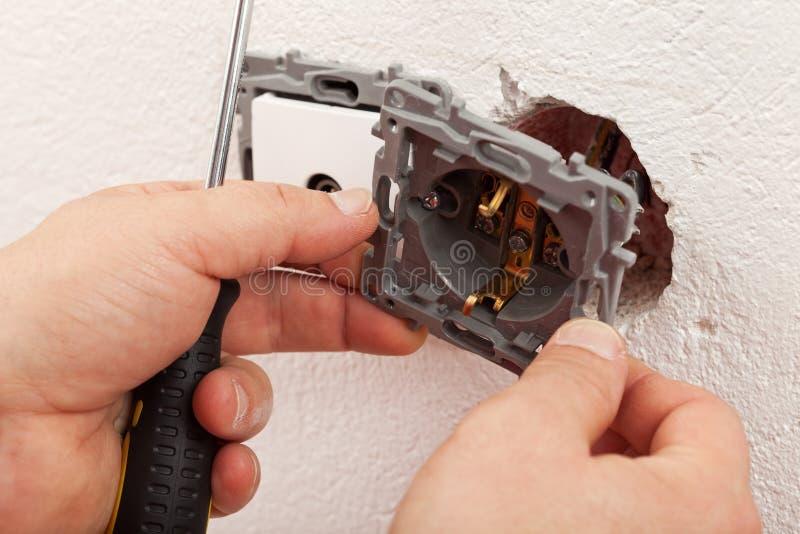 Elektricienhanden die elektrische muurinrichting opzetten stock afbeeldingen