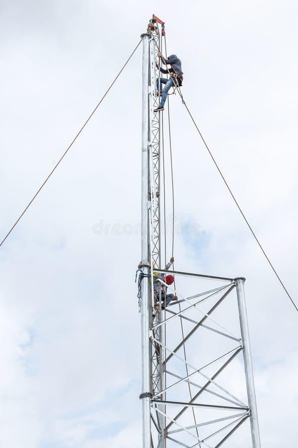 Elektriciens die in de hoogte voor de mededeling van de installatieantenne werken stock foto's