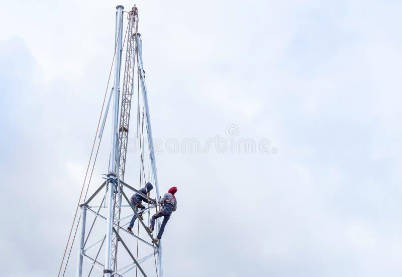 Elektriciens die in de hoogte voor de mededeling van de installatieantenne werken stock afbeelding