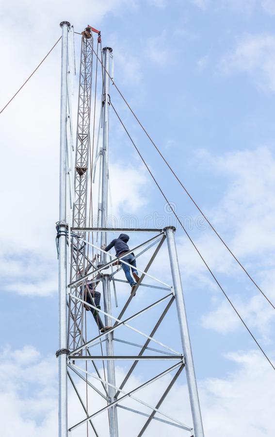 Elektriciens die in de hoogte voor de mededeling van de installatieantenne werken stock fotografie