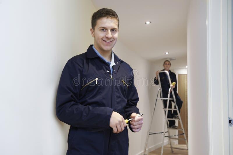 Elektriciens die Plafondlichten installeren in Binnenlands Huis royalty-vrije stock foto