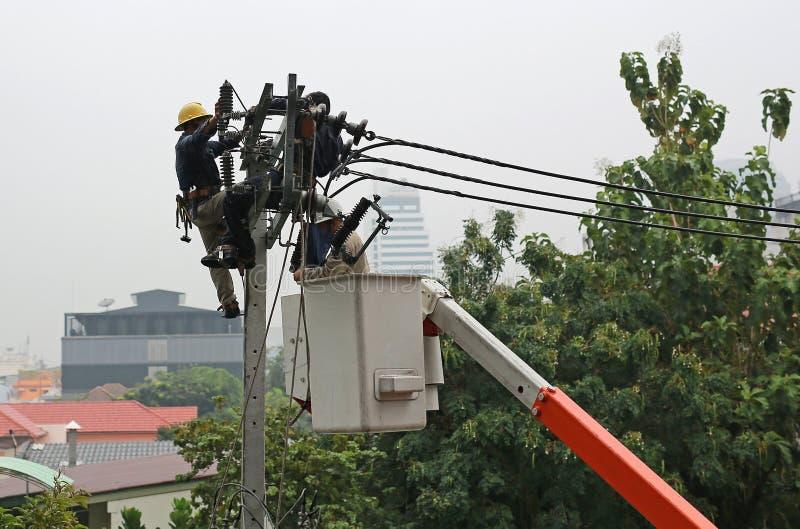 Elektriciens die terwijl het werken om de elektroisolatie op de elektriciteitspool te vervangen rusten stock afbeelding