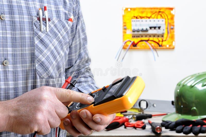 Elektricientechnicus aan het werk aangaande een woon elektrisch systeem stock afbeelding