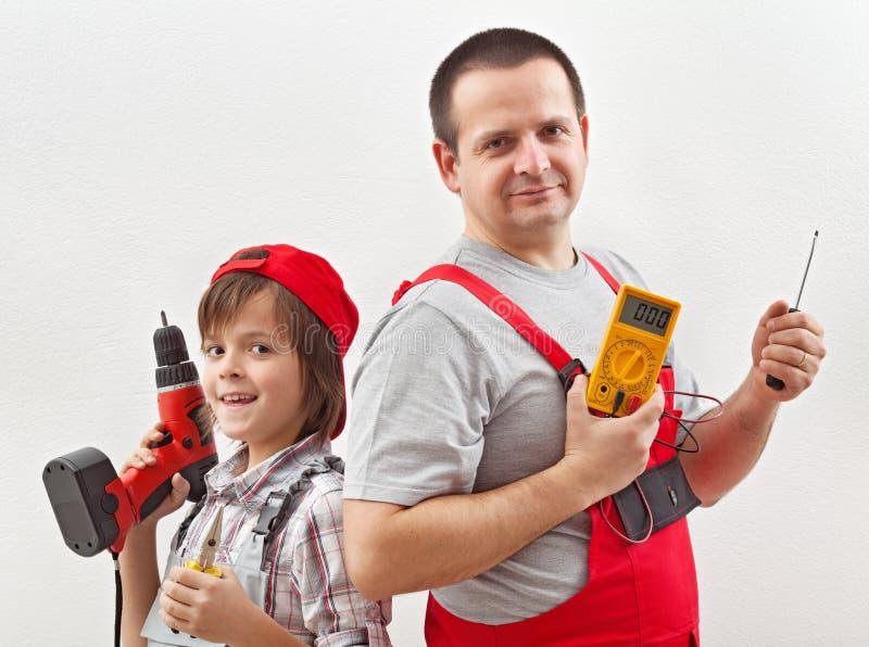 Elektricienvader en het helpen van zoon klaar voor het werk stock fotografie