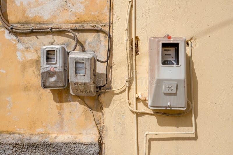 Elektriciteitsmeters op een muur in Benitses op Korfu in Griekenland stock foto