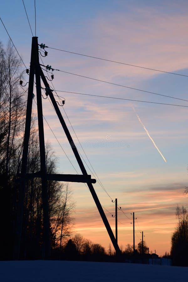 Elektriciteitspolen op de winter rond zonsondergangtijd stock foto