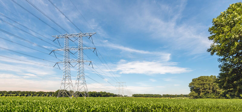 Elektriciteitspylonen en kabels in een landbouwlandschap met royalty-vrije stock afbeeldingen