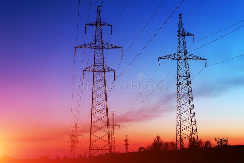 Elektriciteitspylonen en lijnen bij schemer bij zonsondergang royalty-vrije stock fotografie